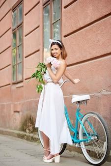 Uśmiechnięta młoda kobieta w biel sukni pozuje z peoniami blisko błękitnego roweru przed czerwonym dziejowym budynkiem