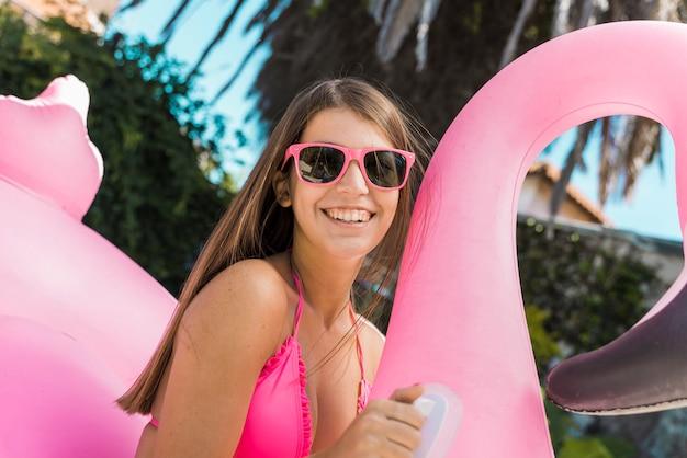 Uśmiechnięta młoda kobieta w bikini na nadmuchiwanym flamingu