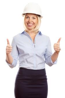 Uśmiechnięta młoda kobieta w biurze ubrania i hełm budowy na głowie. kciuki w górę. pionowy