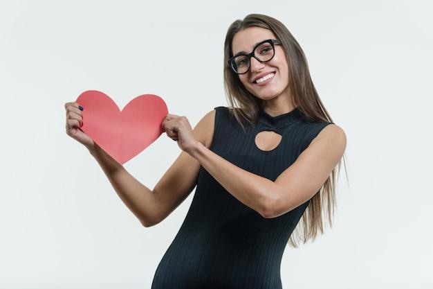 Uśmiechnięta młoda kobieta w czarnej sukni gospodarstwa czerwone serce papieru