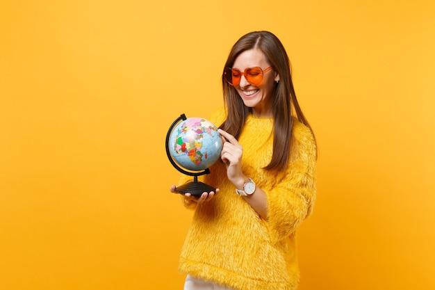 Uśmiechnięta młoda kobieta w futrzanym swetrze i pomarańczowym sercu okulary trzymając palec na świecie na białym tle na jasnym żółtym tle. ludzie szczere emocje, koncepcja stylu życia. powierzchnia reklamowa.