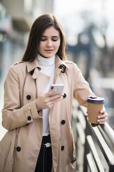 Uśmiechnięta młoda kobieta w jasnobrązowym płaszczu czytać wiadomości na telefon na zewnątrz