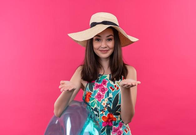 Uśmiechnięta młoda kobieta w kapeluszu, trzymając pierścień do pływania i pokazując puste ręce na odosobnionej różowej ścianie