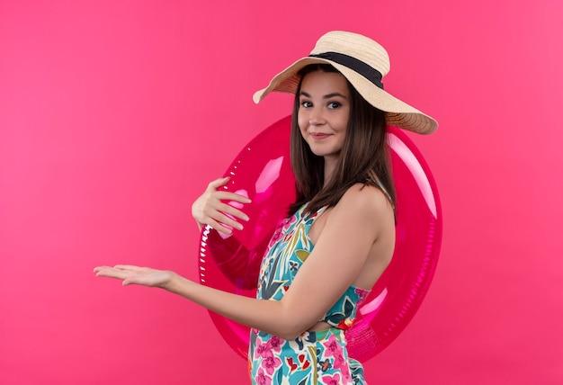 Uśmiechnięta młoda kobieta w kapeluszu, trzymając pierścień do pływania i wskazując ręką po lewej stronie na na białym tle różowej ścianie
