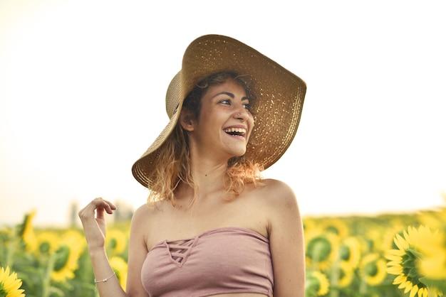 Uśmiechnięta młoda kobieta w kapeluszu w słonecznikowym polu - pojęcie szczęścia