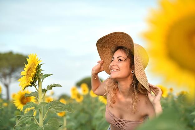 Uśmiechnięta młoda kobieta w kapeluszu w słonecznikowym polu