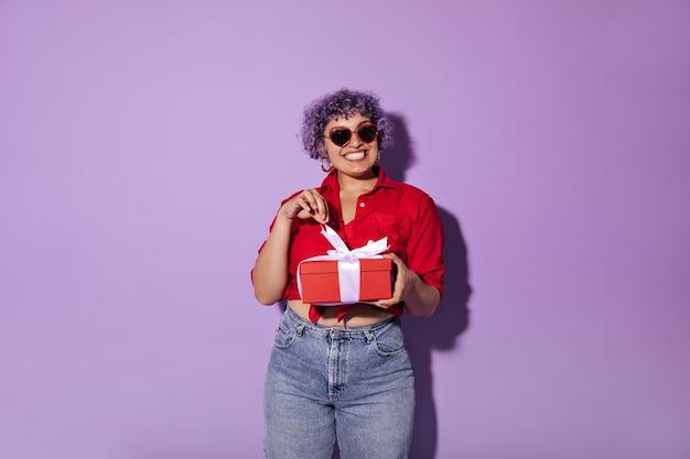 Uśmiechnięta młoda kobieta w okularach przeciwsłonecznych z czerwoną obwódką, w okrągłych złotych kolczykach i czerwonej koszulce cieszy się z jej prezentu na liliowym kolorze.