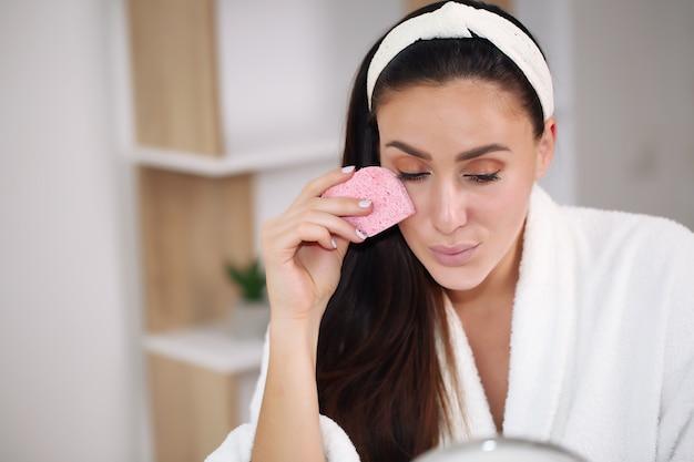 Uśmiechnięta młoda kobieta w opasce do włosów, dotykając jej twarzy i patrząc w lustro w łazience w domu.