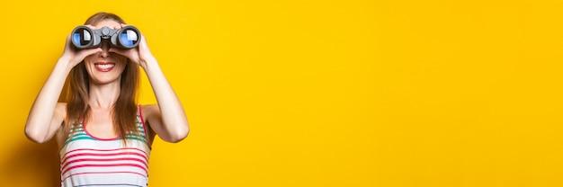 Uśmiechnięta młoda kobieta w pasiastej sukience patrząc przez lornetkę na żółtej przestrzeni. transparent