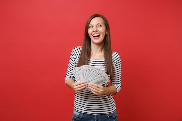 Uśmiechnięta młoda kobieta w pasiastych ubraniach marzy, patrząc w górę, trzymając pakiet wiele dolarów, gotówkę na białym tle na tle czerwonej ściany. ludzie szczere emocje, koncepcja stylu życia. makieta miejsca na kopię.