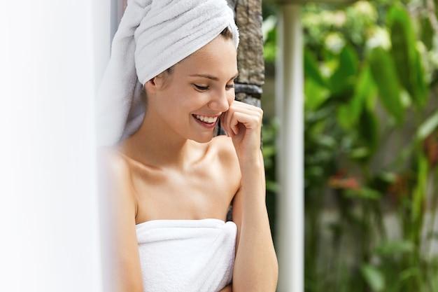 Uśmiechnięta młoda kobieta w ręcznikach