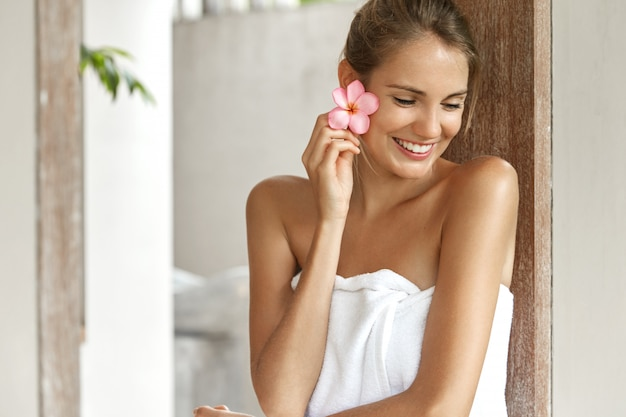 Uśmiechnięta młoda kobieta w ręczniku