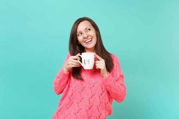 Uśmiechnięta młoda kobieta w różowy sweter z dzianiny patrząc w górę i trzymać w rękach filiżankę kawy lub herbaty na białym tle na tle niebieskiej ściany turkus, portret. koncepcja życia ludzi. makieta miejsca na kopię.