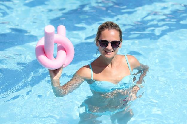 Uśmiechnięta młoda kobieta w stroju kąpielowym robi aqua aerobik turyści są zaangażowani w aerobik w wodzie w
