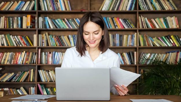 Uśmiechnięta młoda kobieta w stylowej białej bluzce pracuje z papierami w pobliżu współczesnego laptopa przy stole na tle dużych regałów bibliotecznych pełnych książek