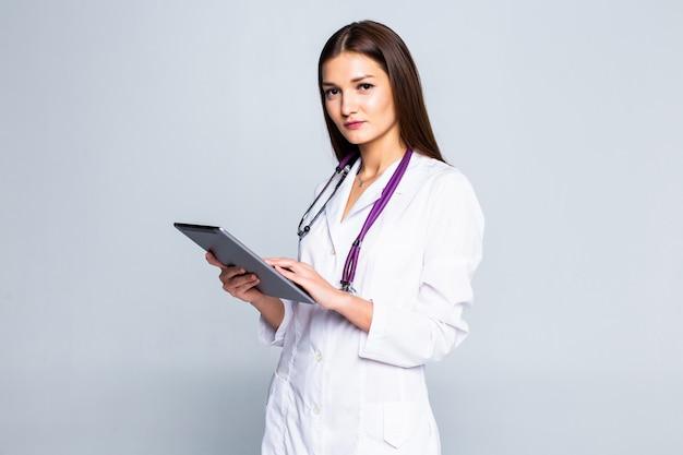 Uśmiechnięta młoda kobieta w sweter, szalik przy użyciu komputera typu tablet komputer, rozmowy wideo na białym tle na szarej ścianie. zdrowy styl życia, konsultacje dotyczące leczenia online, koncepcja zimnej pory roku.