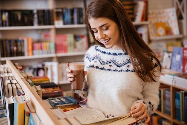 Uśmiechnięta młoda kobieta w swetrze czytająca książkę i pijąca kawę w bibliotece