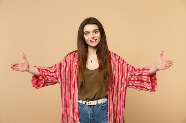 Uśmiechnięta młoda kobieta w zwykłych ubraniach, wskazując rozmiar z poziomym obszarem roboczym na tle pastelowych beżowych ścian. ludzie szczere emocje, koncepcja stylu życia. makieta miejsca na kopię.