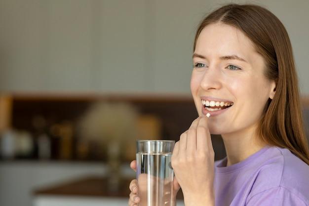 Uśmiechnięta młoda kobieta wkłada do ust kapsułkę suplement diety lub antybiotyk przeciwdepresyjny. skopiuj miejsce