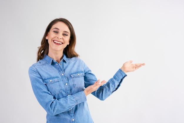 Uśmiechnięta, młoda kobieta, wskazując na miejsce na kopię