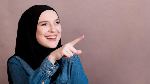 Uśmiechnięta młoda kobieta wskazuje przy coś nad prostym tłem