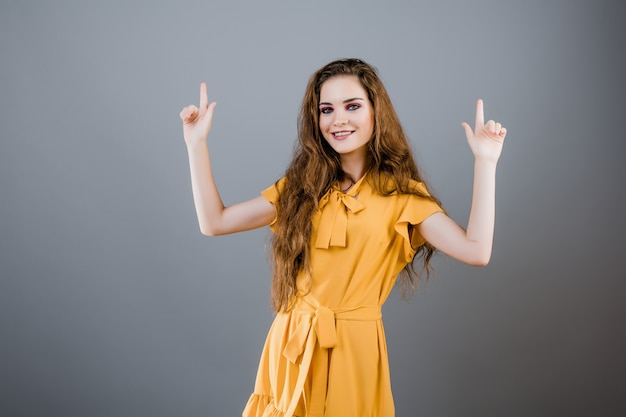 Uśmiechnięta młoda kobieta wskazuje up przy copyspace odizolowywającym