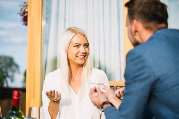 Uśmiechnięta młoda kobieta wzrusza ramionami podczas gdy jego chłopak daje jej pierścionkowi zaręczynowemu
