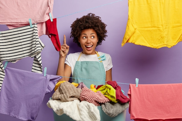 Uśmiechnięta młoda kobieta z afro pozowanie z praniem w kombinezonie