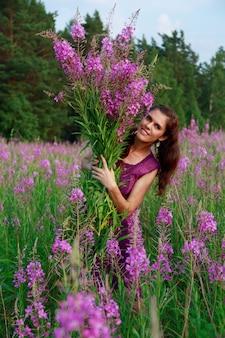 Uśmiechnięta młoda kobieta z bukietem różowych kwiatów w polu