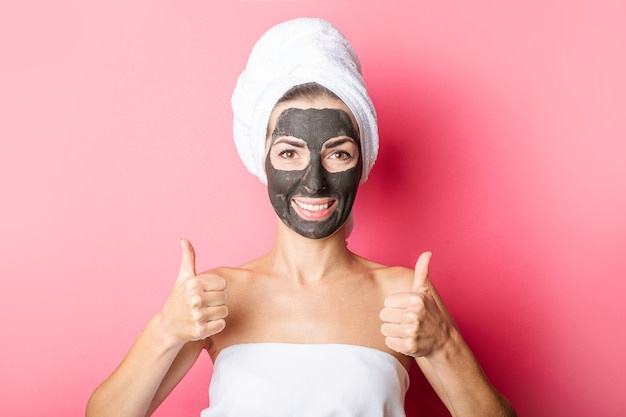 Uśmiechnięta młoda kobieta z czarną maską na różowym tle pokazując kciuk do góry gest.