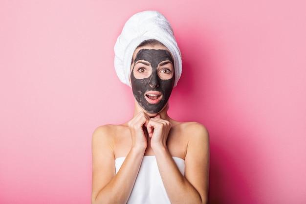 Uśmiechnięta młoda kobieta z czarną maską na różowym tle.