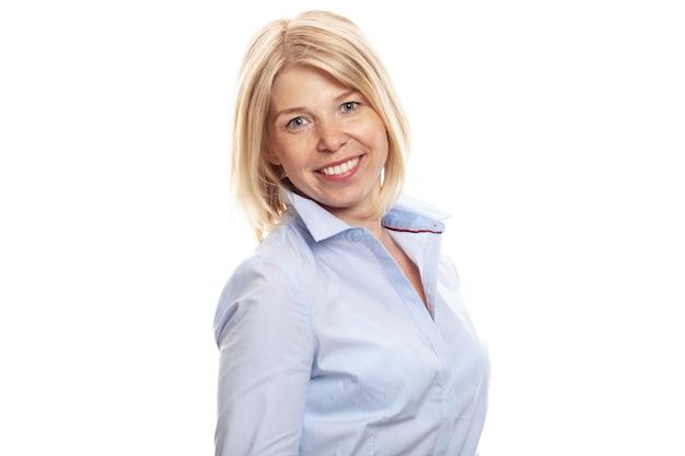 Uśmiechnięta młoda kobieta z piegami na jej twarzy. ubrany w niebieską koszulę w stylu biznesowym. pojedynczo na białym tle.