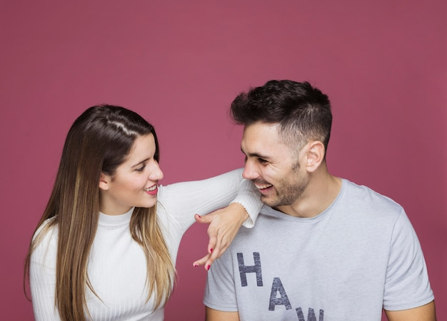 Uśmiechnięta młoda kobieta z ręką na ramieniu mężczyzny