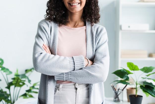 Uśmiechnięta młoda kobieta z rękami krzyżować w biurze