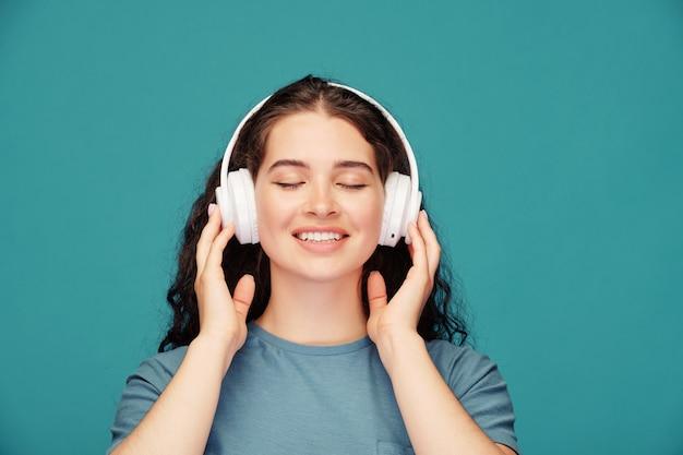 Uśmiechnięta młoda kobieta z zamkniętymi oczami, trzymając słuchawki, ciesząc się ulubioną piosenką na niebiesko