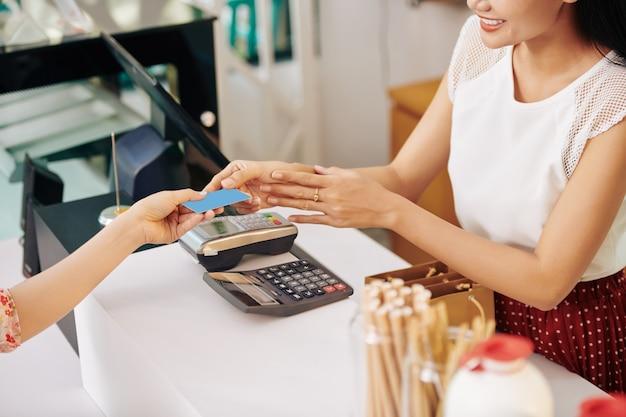 Uśmiechnięta młoda kobieta za pomocą karty kredytowej przy płaceniu za zamówienie w kawiarni