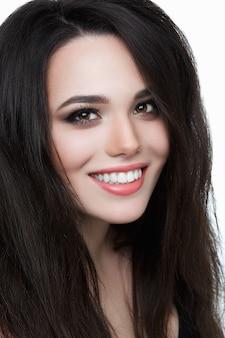 Uśmiechnięta młoda kobieta ze zdrowymi zębami, brunetka portret uśmiechnięty szeroko, śnieżnobiały uśmiech. pure beauty.shot pięknej dziewczyny uśmiechającej się szeroko. piękna kobieta z białym idealnym uśmiechem patrząc na kamery