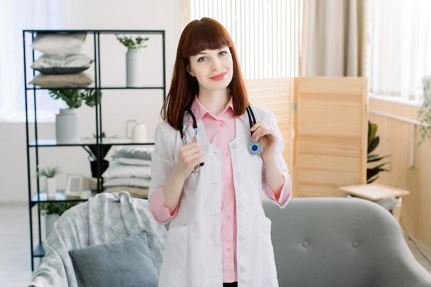 Uśmiechnięta młoda kobiety lekarka z stetoskopem na jej szyi, życzliwy pozytywny kobieta pediatra odwiedza klienta daje domowej konsultaci. pojęcie opieki zdrowotnej