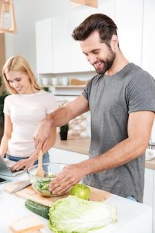 Uśmiechnięta młoda kochająca para gotuje wpólnie używać laptop