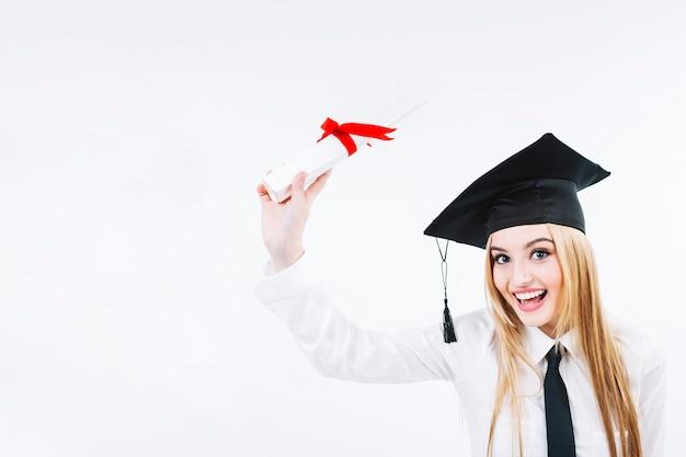 Uśmiechnięta młoda kończy studia kobieta z dyplomem