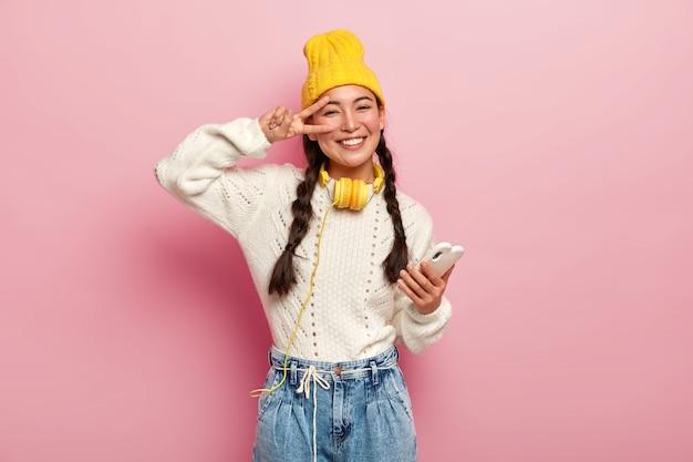 Uśmiechnięta młoda koreanka robi gest pokoju nad okiem, trzyma nowoczesny telefon komórkowy, ma dwa warkocze, uśmiecha się delikatnie, nosi żółty kapelusz i dżinsy, pozuje na różowym tle.