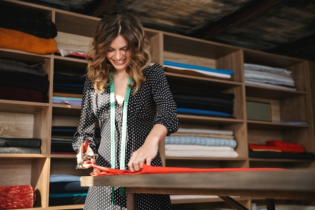 Uśmiechnięta młoda krawcowa kobieta pracuje w warsztacie, pracuje z tkaniny tekstylnej