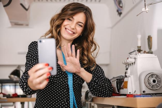 Uśmiechnięta młoda krawcowa kobieta pracuje w warsztacie, przy użyciu maszyny do szycia, biorąc selfie
