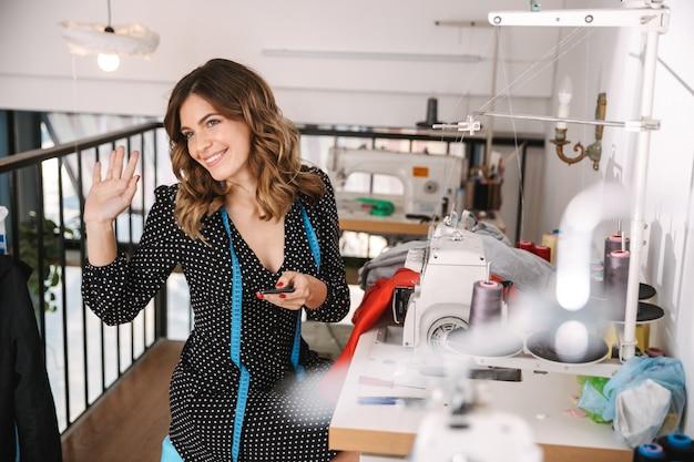 Uśmiechnięta młoda krawcowa kobieta pracuje w warsztacie, przy użyciu maszyny do szycia, macha ręką