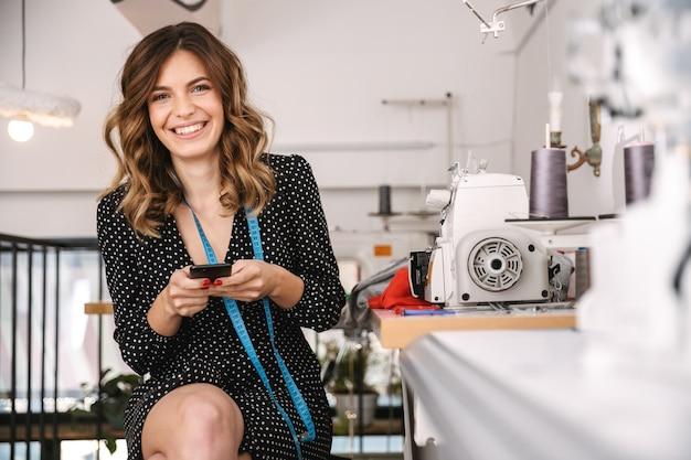 Uśmiechnięta młoda krawcowa kobieta pracuje w warsztacie, przy użyciu maszyny do szycia, przy użyciu telefonu komórkowego