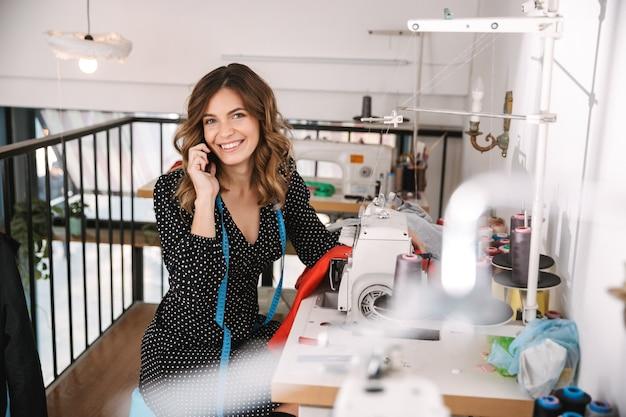Uśmiechnięta młoda krawcowa kobieta pracuje w warsztacie, przy użyciu maszyny do szycia, rozmawia przez telefon komórkowy