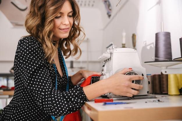 Uśmiechnięta młoda krawcowa kobieta pracuje w warsztacie, przy użyciu maszyny do szycia
