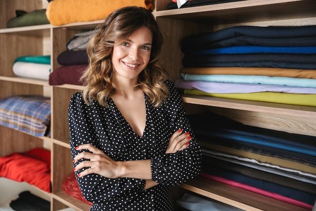 Uśmiechnięta młoda krawcowa kobieta pracuje w warsztacie, wybierając tekstylia