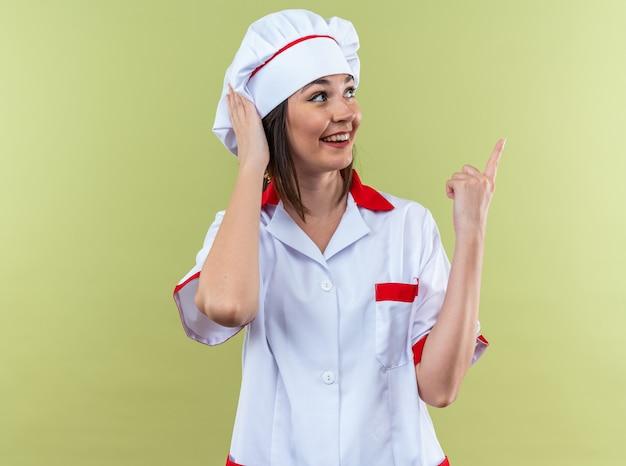 Uśmiechnięta młoda kucharka ubrana w jednolite punkty szefa kuchni z boku na oliwkowozielonej ścianie z kopią miejsca