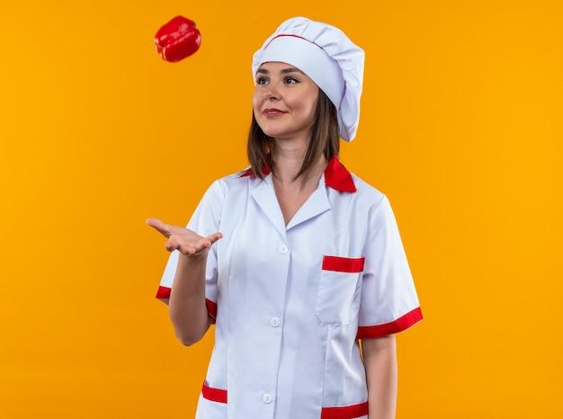 Uśmiechnięta młoda kucharka ubrana w mundur szefa kuchni rzucający pieprzem odizolowana na pomarańczowej ścianie
